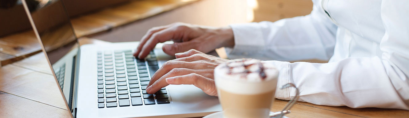 hands typing on laptop with latte