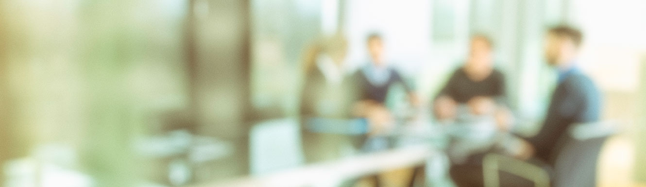 blurred people sitting at conference table